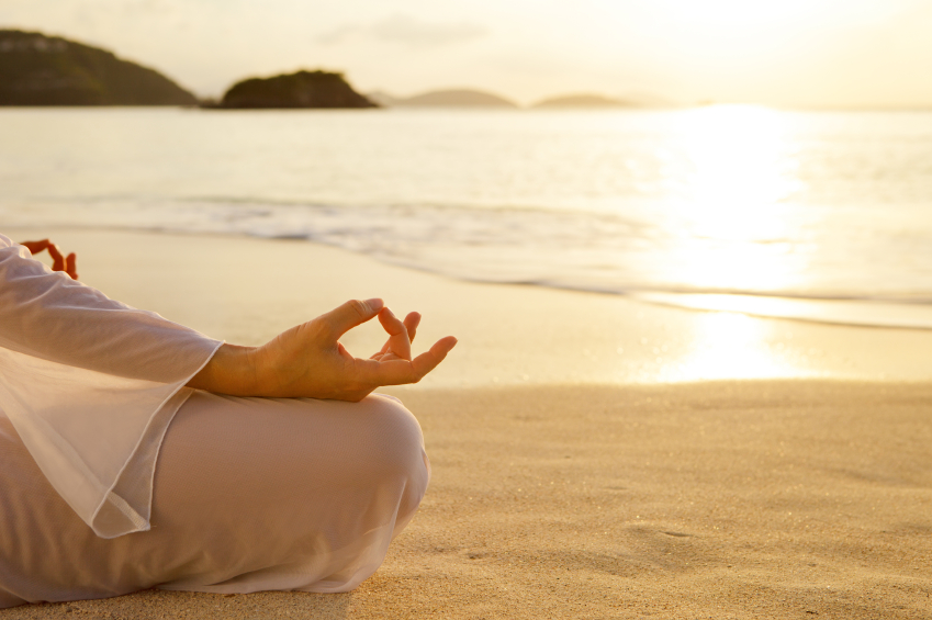 unrecognizable woman meditating at sunset on the beach in the Caribbean