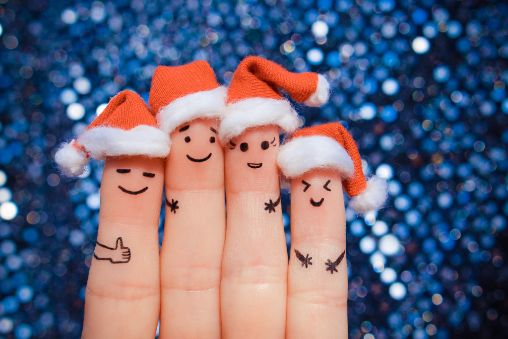Finger art of friends celebrates Christmas. The concept of a group of people laughing in new year hats.