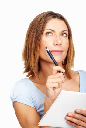 Beautiful business woman thinking while writing on notepad